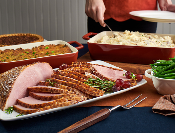 A tray of ham, with stuffing, pie, mashed potatoes and green beans