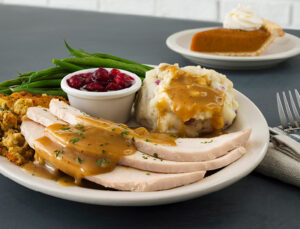 Plate of turkey, mashed potatoes, gravy, green beans, stuffing and cranberries, with a slice of pie